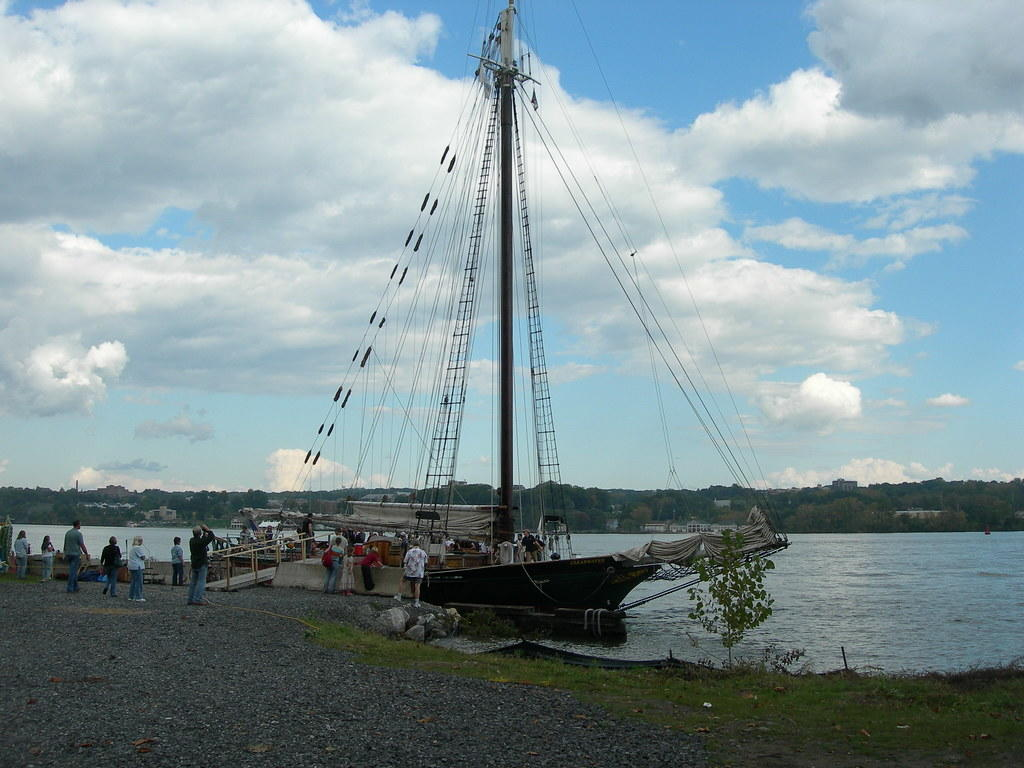 Image description: Sloop Clearwater docked on shore with visitors.